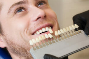 Young man in dental chair choosing color for cosmetic dentistry procedure